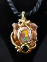 Mexican boulder opal (or fire opal), on a copper splash, with a smokey quartz accent. Wrapped in 14 Kt gold filled wire.